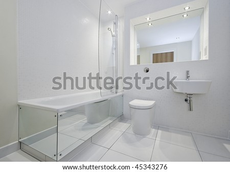 modern bathroom in white with bath tub and shower attachment - stock photo