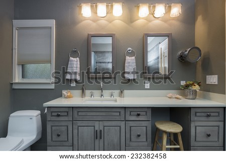 Modern bathroom interior in grey with white marble counter top lights and one chair.  - stock photo