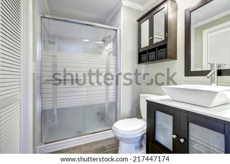 Modern bathroom interior with glass door shower. Brown vanity cabinet with white vessel sink and mirror - stock photo