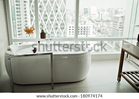 Modern Bathroom interior with white bathtub against huge window with city view