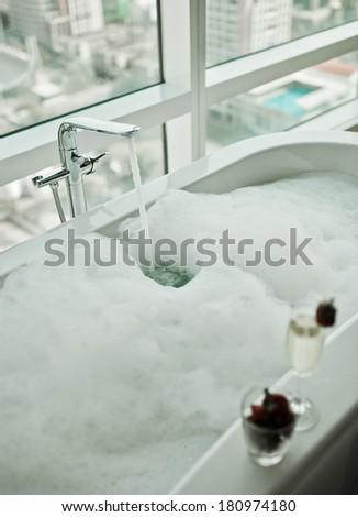 Modern Bathroom interior with white bathtub against huge window with city view - stock photo