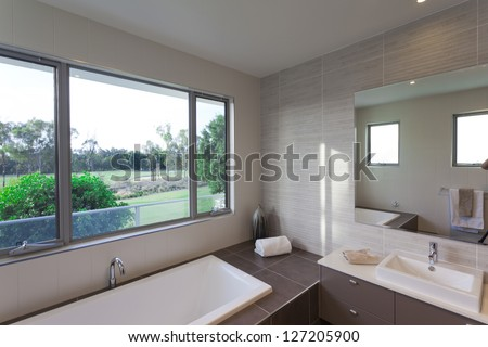 Modern bathroom over looking a golf course - stock photo