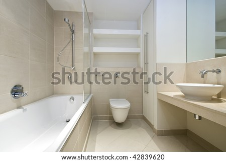 modern bathroom with beige tiles and beige marble - stock photo