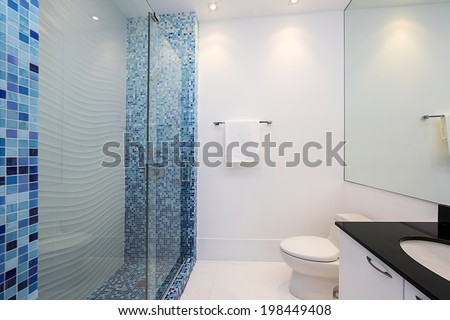 Modern Bathroom with blue shaded mosaic tiles, glass shower and black counter top. - stock photo