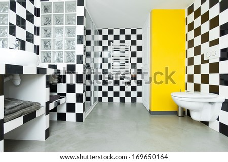 Modern bathroom with checkered black and white tiles on walls.