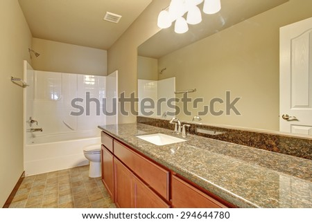 Modern bathroom with full bath shower, and tile floor, also including large counter tops. - stock photo