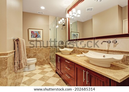 Modern bathroom with glass screened shower and bathroom vanity cabinet with two white vessel sinks and mirror