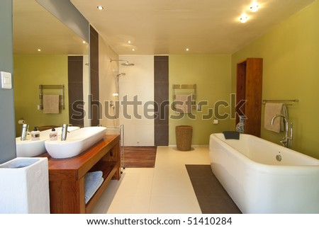 Modern bathroom with pastel coloured walls and white bath. There's also a wood floored open shower