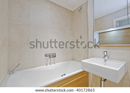 modern bathroom with white ceramic appliances and beige tiles - stock photo