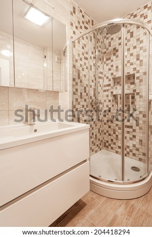 Modern bathroom with white furniture and stone tiles - stock photo