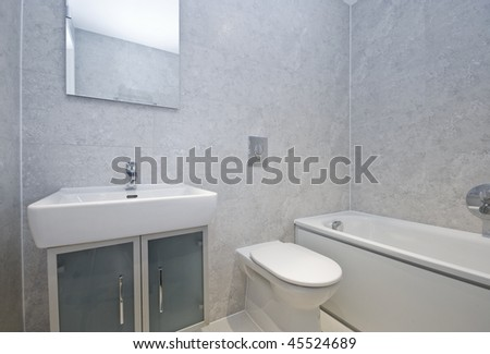 modern bathroom with white porcelain suite and stone imitation tiles - stock photo