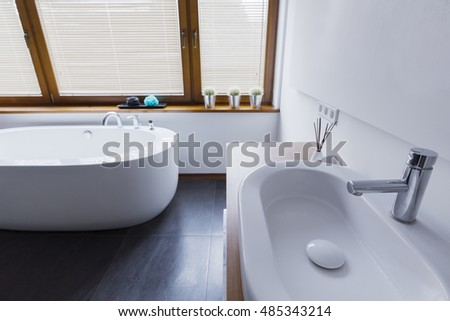 Modern bathroom with white walls, dark tiles on the floor, snowy-white bathtub, sink and window