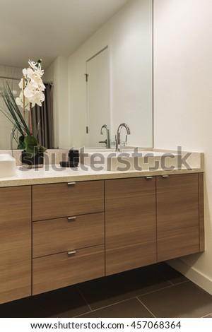 Modern bathroom with wood accent cabinet and solid surface counters