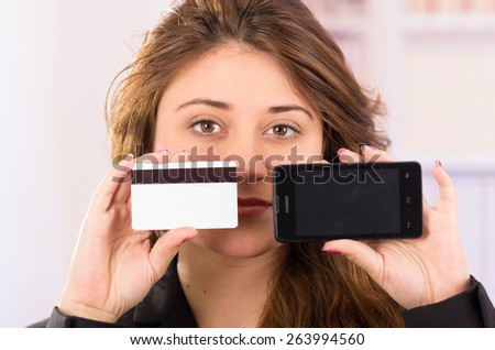 modern beautiful young woman holding cell phone and credit card concept of online shopping, phone purchase - stock photo