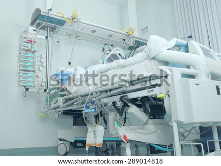 Modern bed in the intensive care with patient - stock photo