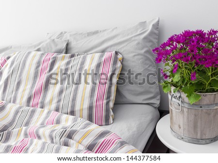 Modern bedroom decorated with bright purple flowers. Fresh design. - stock photo