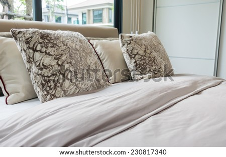 modern bedroom design with bed, pillows and lamp on table - stock photo