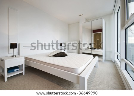 modern bedroom in white with floor to ceiling windows - stock photo