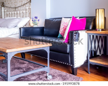 Modern bedroom interior decorated with vintage black leather couch - stock photo