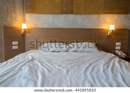 Modern Bedroom, interior design with used bed, pillow, blanket, lamp.