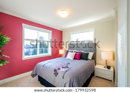 Modern bedroom interior with a red wall, designer pillows, and a floral duvet cover in a luxury house - stock photo