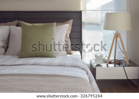 modern bedroom interior with green pillow and decorative wooden lamp on bedside table - stock photo