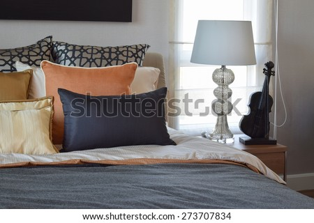 modern bedroom interior with orange and gold pillows on bed and bedside table lamp - stock photo