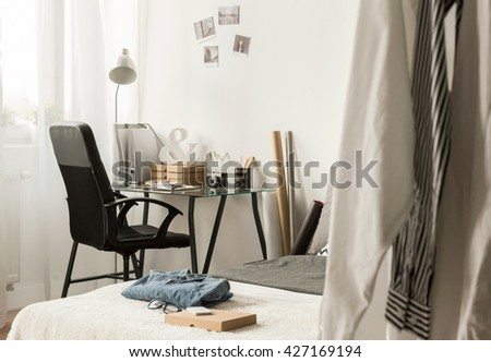 Modern bedroom of a young designer, arrangged in light colours with a lot of personal items