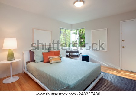 Modern Bedroom of holiday villa with view window blue bed cover and color mixed pillows. - stock photo