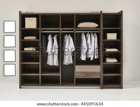 modern bedroom shirts and dress hanging on rail in wooden wardrobe at home