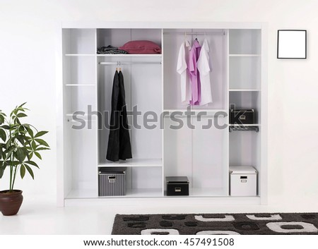 modern bedroom shirts and dress hanging on rail in wooden wardrobe at home - stock photo