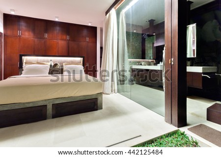 Modern bedroom that exposed to outside covered with glass and illuminated with lights - stock photo