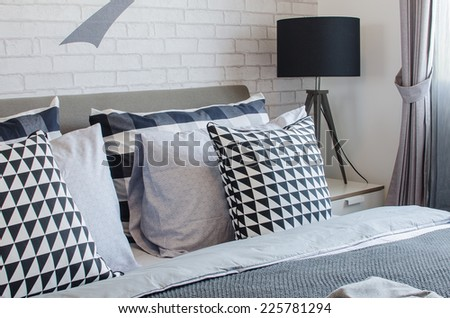 modern bedroom with black and white pillows and black lamp at home - stock photo