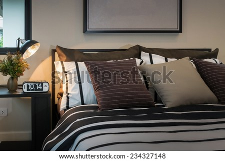 modern bedroom with brown, black and white striped pillows