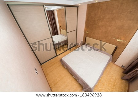 Modern bedroom with closet, large mirror and bed. - stock photo