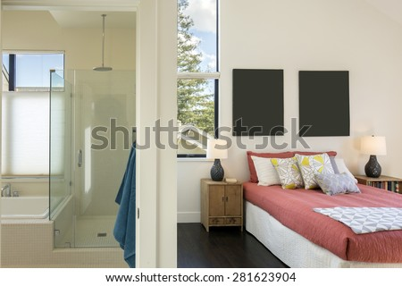 Modern bedroom with high ceiling, red bed sheet cover and pillows right next to modern bathroom with glass shower and bath tub. - stock photo