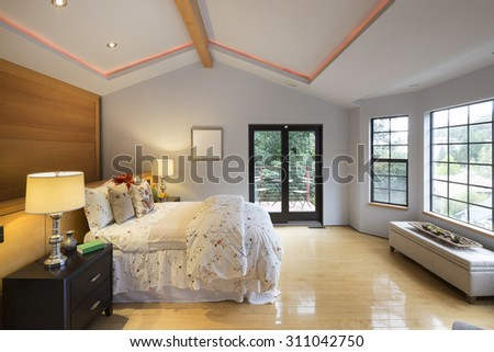 Modern bedroom with illuminated peaked ceiling, bench, wooden floor and wooden accent wall.  - stock photo