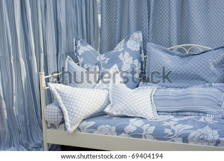 Modern bedroom with lightblue curtains and textured cushions.