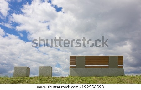 Modern bench and two marble seats on a dam along a river - stock photo