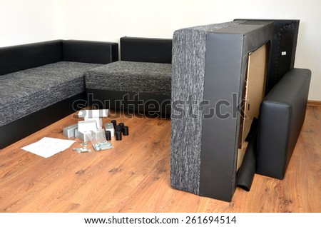 Modern black and white cloth sofa assembly, assembling parts of sofa on brown wooden floor with paper instruction - stock photo