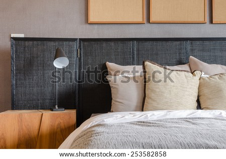 modern black bed with pillows and lamp in bedroom at home - stock photo