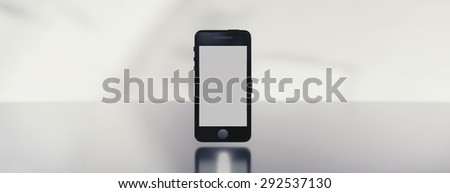 Modern black smartphone on reflective steel surface. Image easy to crop to achieve empty space for text on right or left side.