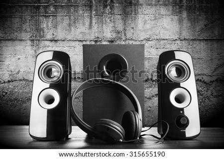 Modern black sound speakers and headphones on dark background - stock photo