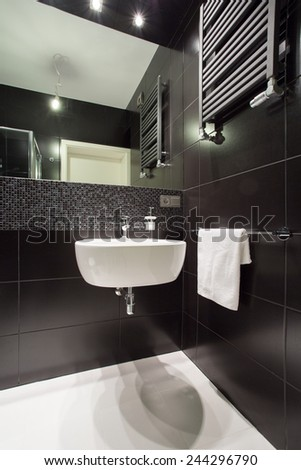 Modern black tiled bathroom in luxury house - stock photo