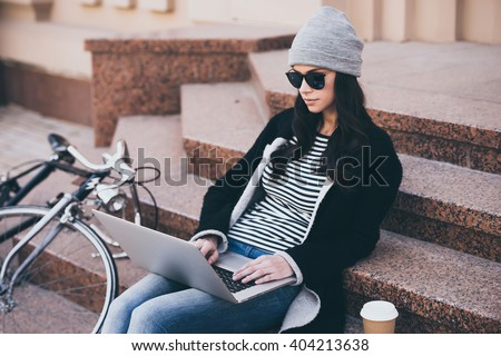 Modern blogger at work. Beautiful young woman in sunglasses using her laptop while sitting on steps outdoors  - stock photo