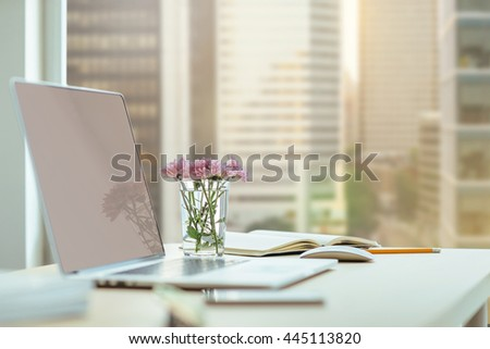 Modern blogger's workplace, Close-up desktop with modern laptop, flowers on the wooden desk. Desktop with a view of downtown, Sunrise, Shallow DOF. Workplace in a skyscraper.  - stock photo