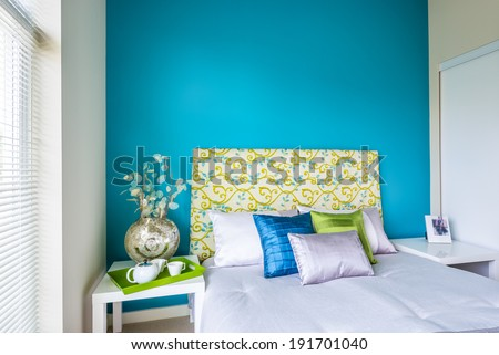 Modern blue bedroom interior with blue, green, and violet designer pillows in a luxury house. Interior design. - stock photo
