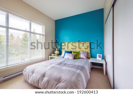 Modern blue bedroom interior with blue, green, and violet designer pillows in a luxury house. Interior design.