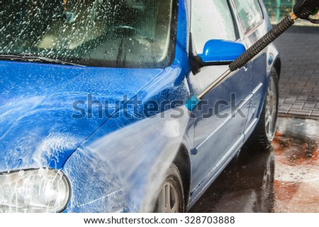 Modern blue car in a car wash