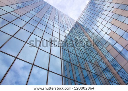 modern blue facade of glass and steel with cloudy sky and reflections - stock photo